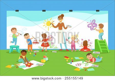Young Children In Art Class Drawing And Painting With Teacher In A Nursery School