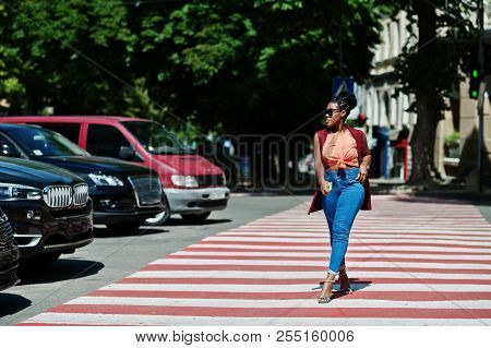 Stylish African American Woman Walking On Crosswalk Or Pedestrian Crossing With Mobile Phone At Hand