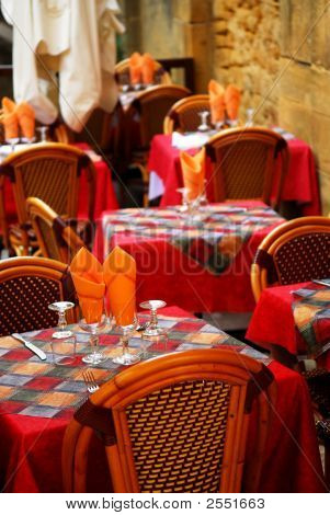 Set tables with tablecloth and glasses on restaurant outdoor patio poster