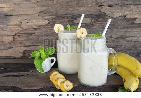 Banana smoothies juice and yellow banana fruit beverage healthy the taste yummy In glass for for milkshake on wooden background. poster
