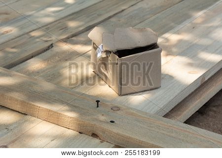 A Box Of Screws On A Wooden Surface, A Formwork For A Fence