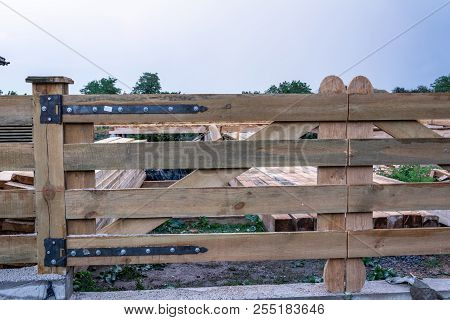Forged Hinges On A Wooden Gate Against A Background Of The Evening Sky After A Rain
