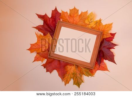 Autumn Composition With Picture Frame And Autumn Maple Leaves On Beige Background. Copy Space.