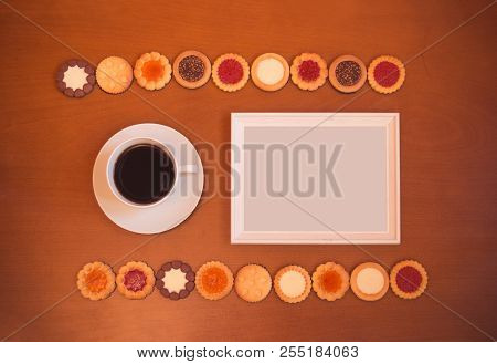 White Frame, Cup Of Coffee And Assortment Of Mixed Biscuits On Rustic Wooden Background. Top View, C
