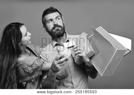 Couple In Love Holds Shopping Bags On Coral Background. Guy With Beard And Lady With Concerned Faces