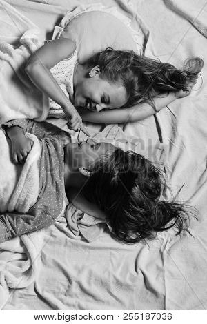 Kids With Happy Faces Lie In Bed. Girl Lies On White And Pink Bed Sheets, Touching Friends Nose. Paj