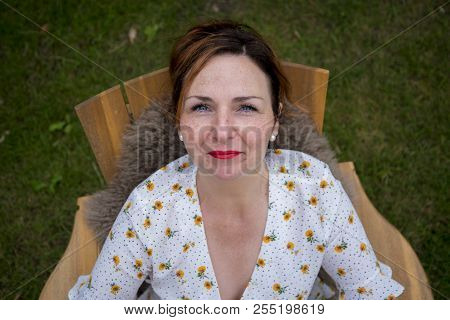 Top View Of A Woman Staring Up To The Camera In A Garden