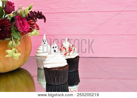 Halloween cupcakes. Spooky ghost bloody cupcakes. Halloween treats on pink wood background. Halloween pumpkin with flowers. Halloween cupcakes background. Halloween background. Halloween monster background. Halloween treats background Halloween background