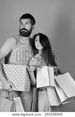 Couple In Love Holds Shopping Bags On Yellow Background. Guy With Beard And Girl With Thoughtful Fac