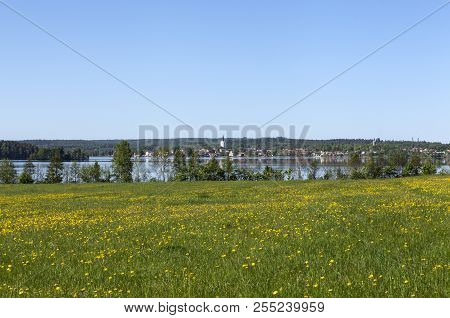 View Of Nora Town From A Distance. Meadows, Flowers, Lake And Buildings. Spring.