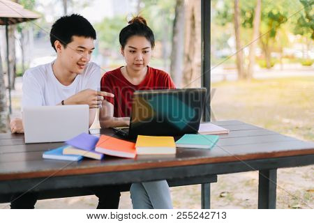 Group Of Asian University Students Reading A Book The Final Exam  By A Tablet And A Laptop On A Wood