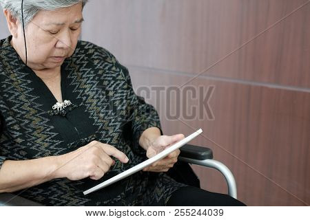 Elder Senior Woman On Wheelchair Holding Tablet. Elderly Female Texting Message, Using App With Touc