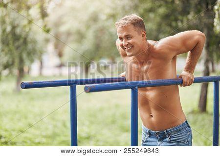 Sideways Shot Of Brawny Strong European Male Wears Jean Shorts, Has Positive Smile, Works Abs On Han