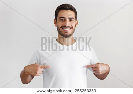 Smiling Nice Man Pointing At Blank White T-shirt With Both Index Fingers, Copy Space For Your Advert