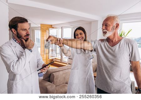 Man having chiropractic arm adjustment. Physiotherapy, sport injury rehabilitation. Senior man exercises in center for chiropractic. poster