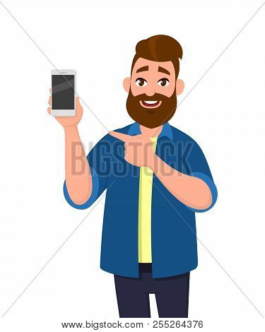 Happy Young Man Showing Smartphone And Pointing Hand Towards The Phone. Mobile Phone Technology Conc