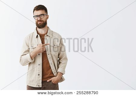 Indifferent displeased adult european male entrepreneur in beige jacket over brown t-shirt and glasses with sick long hipset beard pointing right frowning from scorn and disdain, unimpressed disliking poster