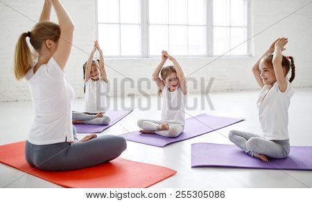 Children Practicing Are Engaged In Gymnastics And Yoga With  Teacher