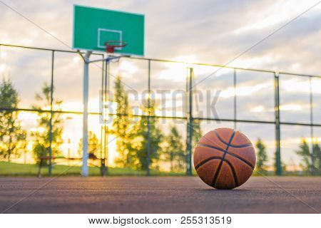 Basketball Court. A Basketball Ball Lies On The Ground In The Background Of A Shield And An Evening