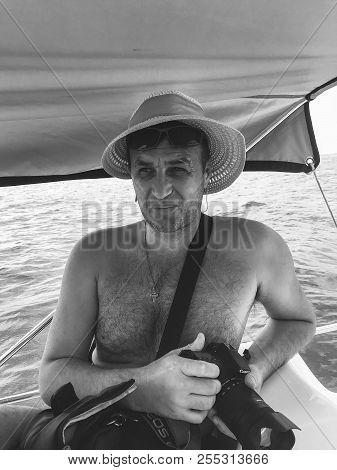 Sochi, Russia - August 25, 2018: Portrait Of A Forty-year-old Man In A Womans Hat With A Camera In H