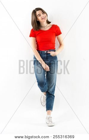 Beautiful Young Girl Wearing Red T-shirt And Jeans Leaning On A Wall On White Background, Studio Sho