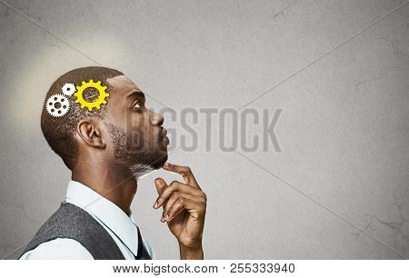 Side view portrait young business man thinking deciding finger on chin looking up gear mechanism over head isolated grey wall background copy space. Emotion facial expression perception intelligence poster