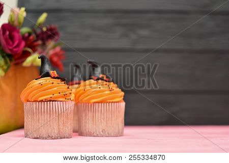 Halloween cupcakes background. Witch's hat cupcake. Halloween treats on wooden pink black background. Halloween pumpkin. Halloween treats background. Halloween monsters party background. Halloween background. Halloween treats on wood background. Halloween