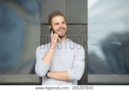 Man With Beard Call Smartphone Urban Background. Guy Happy Smile Use Smartphone To Communicate Frien