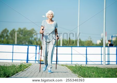 Full Length Portrait Of Active Senior Woman Practicing Nordic Walking With Poles Outdoors In Park, C
