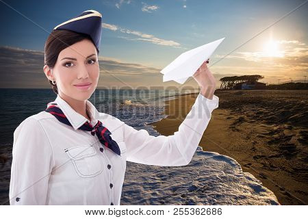 Travel Concept - Beautiful Stewardess With Paper Plane Over Sunset Beach Background