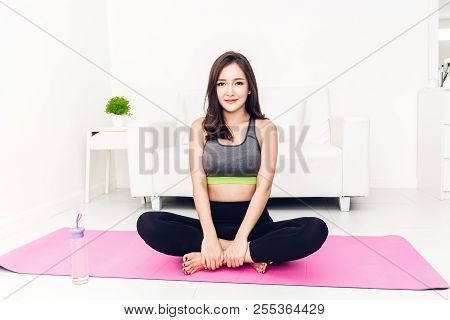 Sport Woman Sitting Relax On Pink Mat And Do Fitness Exercise With Water Bottle At Home.diet Concept
