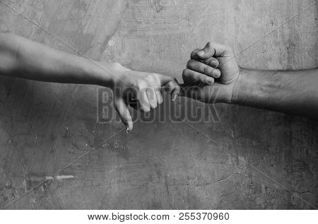 Pinkie promise and friendship. Male and female hands touching each other with little fingers on abstract cement wall on beige background poster