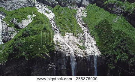 Waterfall Flowing Down From High Mountains On A Sunny Day. Top View Of The Mountain From Which The R