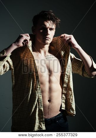 poster of Man with torso, muscular macho with six packs, dressing shirt, dark background. Masculine concept. Guy looks confident and attractive. Macho on pensive face, muscular figure, sportsman, bodybuilder