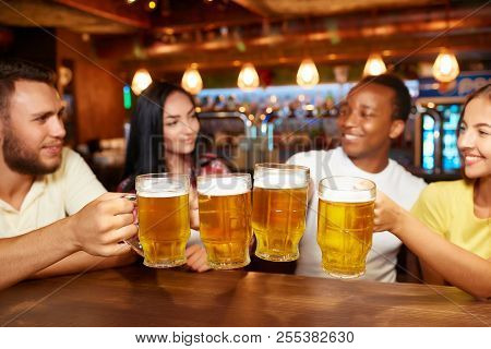 Four Friends Toasting With Glasses Of Light Beer At Pub. Group Of People Drinking Beer, Having Fun T