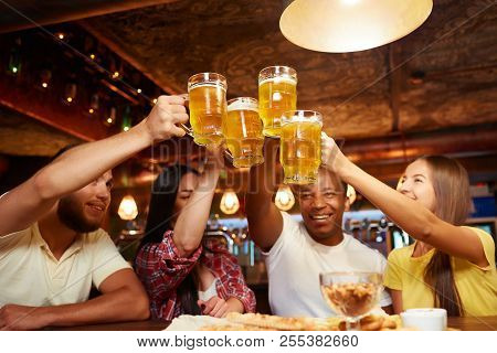 People Raising Beer Glasses High Above Table And Looking On Drink, Having Fun Together. Group Of Hap