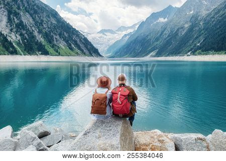 Travelers Couple Look At The Mountain Lake. Travel And Active Life Concept With Team. Adventure And