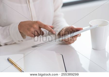 Close-up Of Woman Sitting At Table And Using Digital Tablet. Young Caucasian Businesswoman Searching