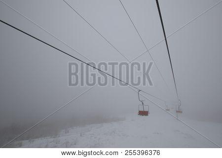 Ski elevator in winter haze with empty seats poster