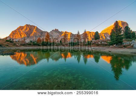Mountain Rocks And Autumn Trees Reflected In Water Of Limides Lake At Sunset, Dolomite Alps, Italy