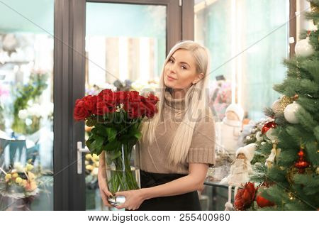 Young woman with bouquet of roses standing in store. Small business owner