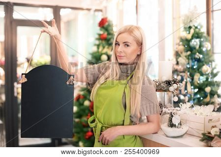 Young woman holding signboard in flower store. Small business owner