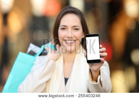 Happy Shopper Showing A Blank Phone Screen Mock Up Outdoors In The Street With A Storefront In The B
