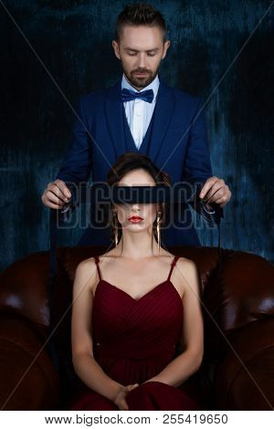Couple In Dating. Rich Man Male Dress Skirt Tying Woman Eyes. Woman Female In Expensive Red Evening