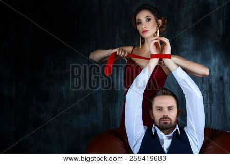 Couple In Dating. Rich Man Male Dressed Skirt Sitting With Tied Hands. Woman Female In Expensive Red