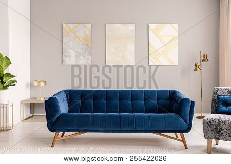 Royal Blue Settee Standing In Real Photo Of Light Grey Living Room Interior With Gold Lamps And Thre