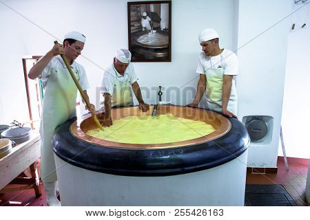 Primiero San Martino Di Castrozza - Italy - July 31, 2018 - A Team Of Cheesemakers At Work In A Dair