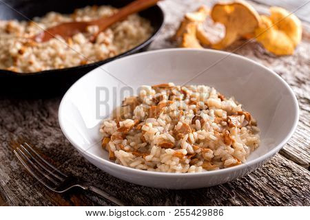 A Bowl Of Delicious Chanterelle Risotto On A Rustic Wood Table Top.