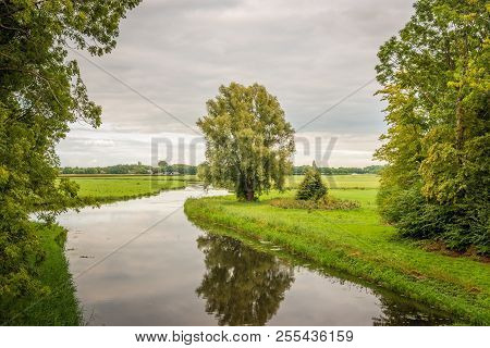 Meandering Brook In A Dutch Landscape. It Is A Windless Day In The Summer Season. The Water Surface