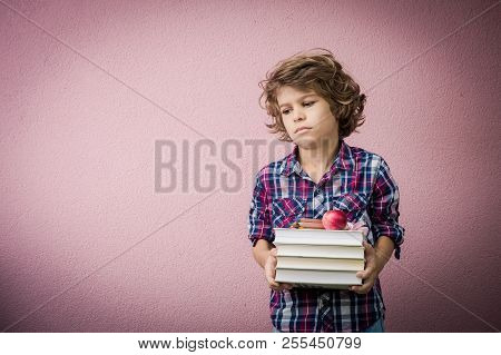 Little Boy Holding Stack Of Books With Read Apple And Pencils Ready To Go Back To School.